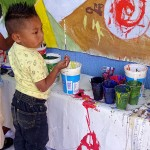 Child painting a mural in the 20th Anniversary of SIPAZ © SIPAZ